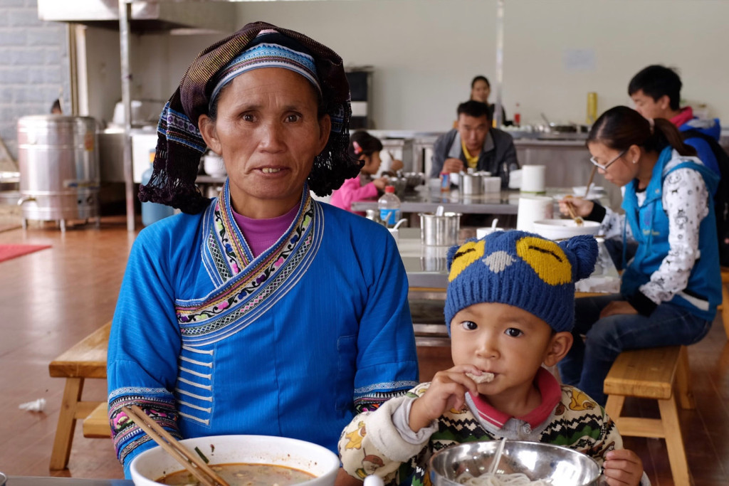 A woman and her grandchild eat noodles in China for breakfast. C