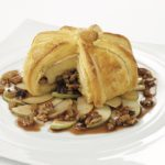 Appetizer with brie, apple, puff pastry and raisins