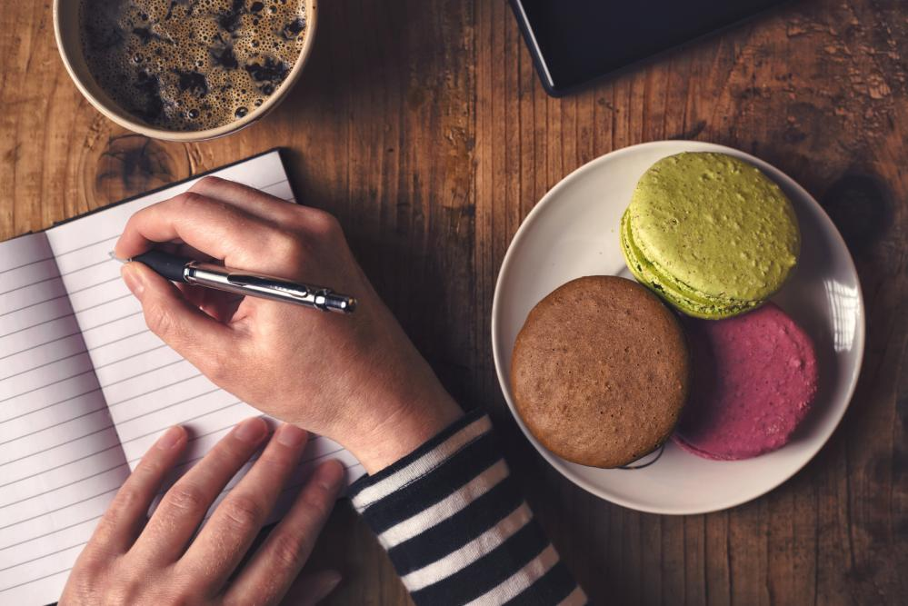 Image of young woman's hands writing in notebook with coffee and macaroons on the table.